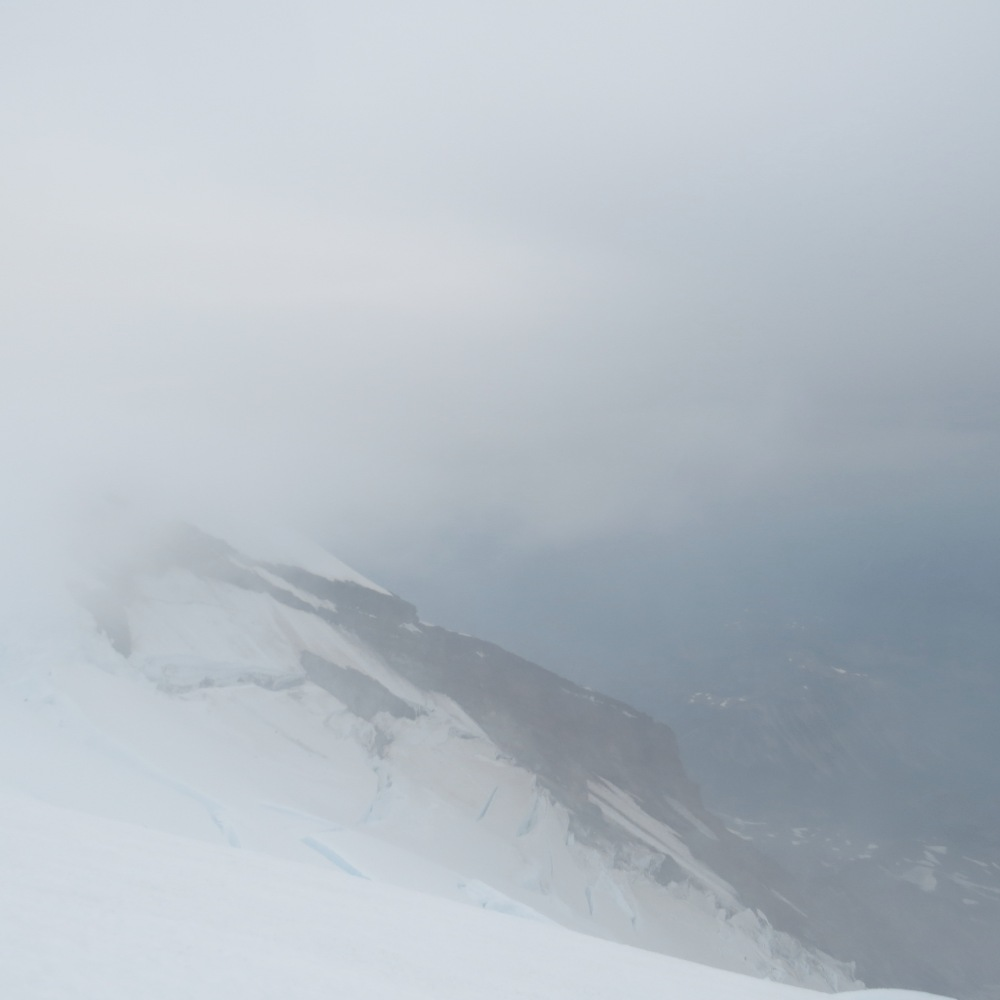 The cloud cover on the upper portion of the mountain.